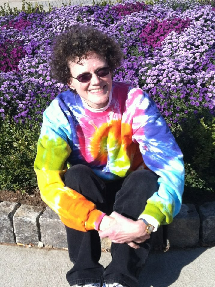 Margaret wearing tie-dye and sitting on the ground in front of purple flowers
