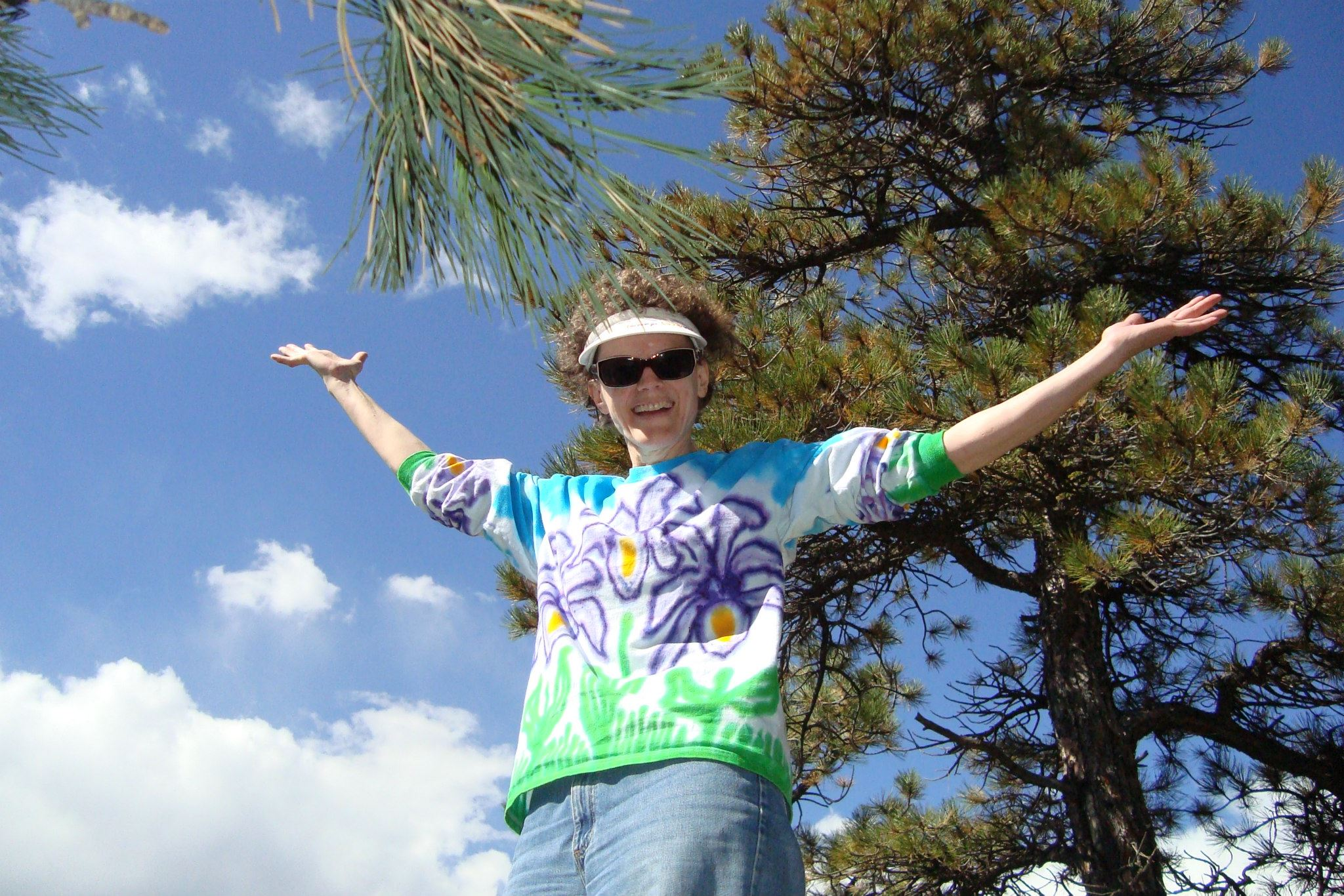 Margaret with arms raised in front of a tree with a blue sky